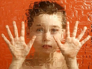 Autistc child looking through pane of glass