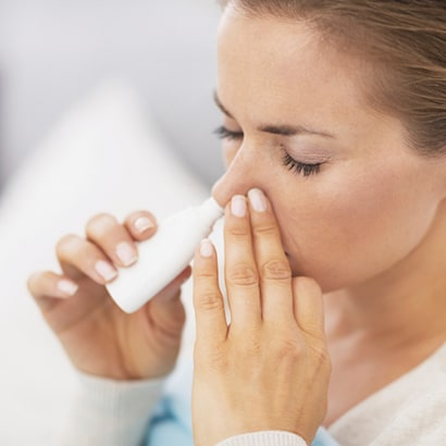 Young woman using epinephrine nasal spray