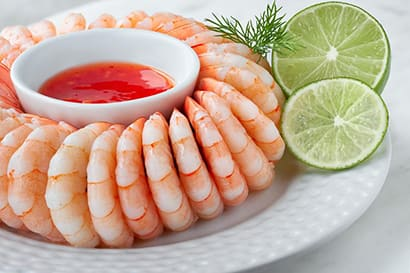 Shrimp with dip and limes on a plate